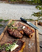 Barbecued beef steaks with butter and rosemary on a wooden board