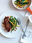 Barbecued beef steak with caramelised beans