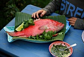 A fresh red snapper with herbs, lying on a banana leaf