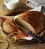 A crusty loaf, sliced open, in a bread basket