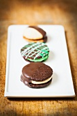 Three Assorted Sandwich Cookies on a White Platter