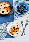 Blueberry and Peach Pie on a Plate and in Baking Dish; Bowl of Fresh Blueberries; Bottle of Milk with a Straw