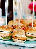 Salmon burgers in sesame seed buns on wooden skewers