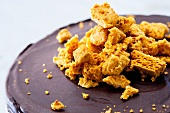 A chocolate cake topped with crumbled pieces of honey cake