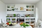 weiße Küchenzeile mit Keramikfliesen; im Vordergrund ein großer Tisch mit frischem Gemüse und einer Edelstahlschüssel voller Couscous