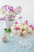 A Glass Footed Bowl Full of Meringue Cookies with Flower Petals; Vase of Flowers in Background