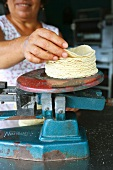 A Woman Placing Corn Tortillas on a Scale