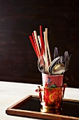 A mix of European and Asian eating implements - chopsticks and cutlery in stacked cups on a wooden tray