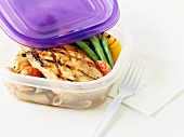 A barbecued chicken breast with vegetables and penne pasta in a food storage box