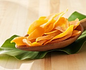 Dried mango slices on a wooden spoon