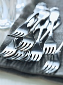 Lots of forks on a linen cloth