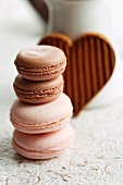 Assorted macaroons in front of a heart-shaped chocolate biscuit