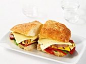 A sandwich with vegetables, ham and Havarti cheese