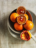 Several Sanguinello blood oranges: whole, halved and squeezed-out rinds