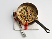 Zürcher Geschnetzeltes (Swiss dish from Zurich consisting of chopped veal, mushrooms and cream) in a copper saucepan