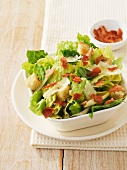 Caesar salad with bacon bits, croutons and parmesan