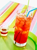 Fruit punch in a glass with drinking straws