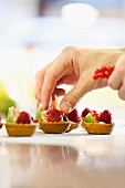 Mini tartlets being topped with fresh fruit