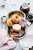 Assorted doughnuts on a tray with coffee cups to one side