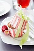 Muffinförmchen als Behälter für Gastgeschenk auf Teller mit Bellisblüte