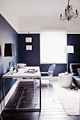 Home Office im Schlafzimmer - moderner Schreibtisch, Acryglas-Stuhl und Tischlampe vor eleganter, blauweiss gestalteter Wand
