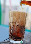 Cola being poured into a glass