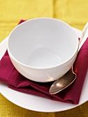 Leere Essschale auf Teller mit Serviette und Löffel
