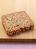 A slice of wholemeal bread on a chopping board