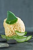 Geschnittenes Aloe Vera Blatt mit Luffaschwamm und Kieselsteinen