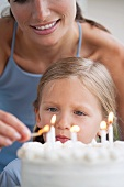 Mother lighting the candles on her daughter's birthday cake