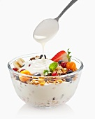 Yoghurt being spooned over a bowl of fruit muesli