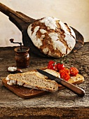 Classic sourdough rye-wheat bread: a whole loaf and slices of bread with cherry tomatoes on a chopping board