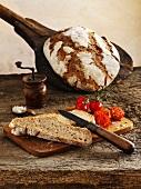 Klassisches Sauerteig-Mischbrot: ganzer Laib und Brotscheiben mit Kirschtomaten auf Schneidebrett