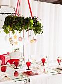 Weihnachtlich dekorierter Kranz von Decke abgehängt über gedeckten Tisch mit roten Retro Weingläsern