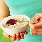 A woman holding a bowl of porridge with jam