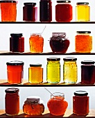 Assorted jars of jam on wooden shelves