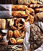 Verschiedene Brote, Brötchen, Brezeln und Croissants auf Pergamentpapier