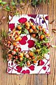 Kranz aus verschiedenen Hagebuttensorten und Spireenzweige in Herbstfärbung