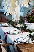 Country-house-style table festively set for Christmas with red and white striped tablecloth and artistic, white paper Advent stars