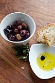 Oliven, Weissbrot und Olivenöl mit Balsamicoessig