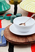 Ceramic crockery and a vintage wooden board on a rustic tablecloth