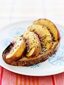 A Slice of Country Bread Topped with Sliced Nectarines and a Honey-Lemon-Poppy Glaze
