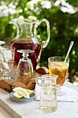Kleiner Glaskrug mit Sirup, Zitronenschnitze und Eistee auf einem Gartentisch