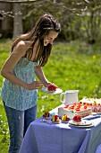 Junge Frau vor Kuchenbüffet im Freien