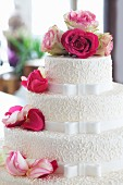 An elegant wedding cake decorated with fresh roses