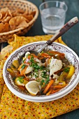 A Bowl of Fish Stew with Carrots and Yellow Bell Pepper