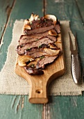Sliced Flank Steak with Onions and Mushrooms on a Cutting Board