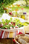 Summer salad with figs and strawberries on a table outdoors