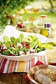 Sommersalat mit Feigen und Erdbeeren auf einem Tisch im Freien