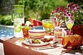 Gedeckter Tisch mit Limonade, Obst und Salat am Pool